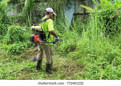Klang Malaysia Nov 18, 2017. Worker cutting grass with grass cutting equipment. Cutting grass and weeds is one way to prevent encroachment of animals and insects like snakes and mosquitoes.
