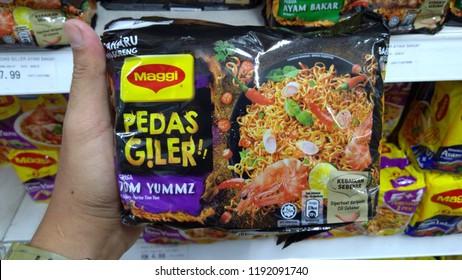 KLANG, MALAYSIA - SEPTEMBER 20, 2018: Hand hold Mee goreng segera Maggi Pedas Giler perisa Tom Yummz dan Ayam Bakar. Maggi Crazy Spicy Tomyam and Grill Chicken flavor.