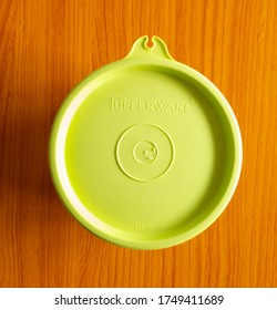 Klang, Selangor, Malaysia: 5th June 2020- Top view of green Tupperware brand isolated on wooden background.