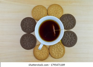 Klang,Malaysia: 14th August 2020- Tea cup and biscuits on a wooden table. Traditional hot drink for breakfast. Tea time. Herbal tonic beverage. Isolated on a black background.