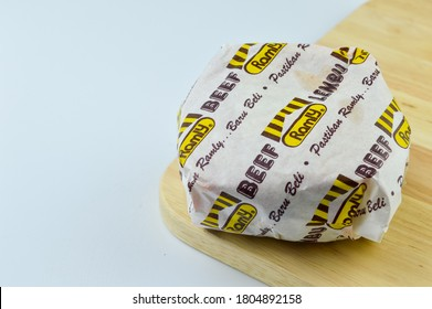 Klang,Malaysia: 29th August 2020- Burger packed in the wrapping paper on wooden chopping board over white background. Hamburger Mock up.High resolution photo.