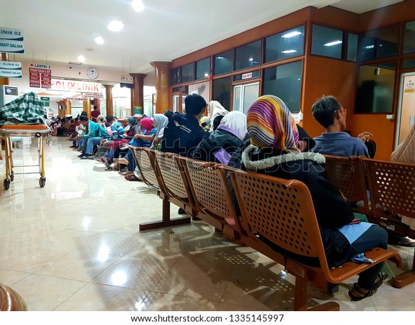 KLATEN, INDONESIA - MARCH 10, 2019 : Some peoples are sitting on a brown chair in waiting room to check their health in a hospital. side view