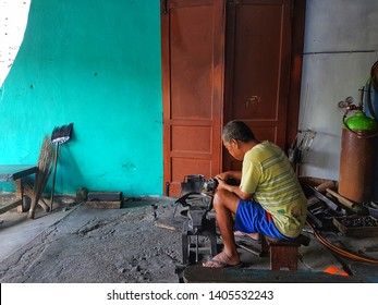 KLATEN, INDONESIA – MAY 23, 2019 :  A man is honing the aluminium motorbike bumper using electric grinder.