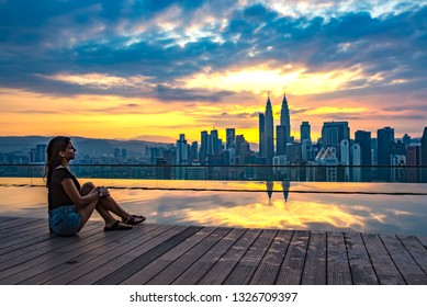 KLCC, Kuala Lumpur, Malaysia - February 7th, 2019: A Girl Sitting By The Swimming Pool Looking at The Skyscrapers in Kuala Lumpur City Centre During Sunrise Time