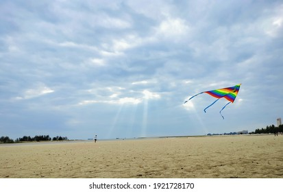 Klebang beach, Malacca, February 21, 2021. The picture of colourful kite flying over the beach, and the blue sky with sunlight going through the cloud.