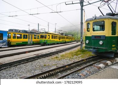 Kleine Scheidegg, Bernese Oberland, Switzerland - July 31 2019 : multiple trains from the Wengernalpbahn (WAB) in the Kleine Scheidegg railway station on a foggy summer day