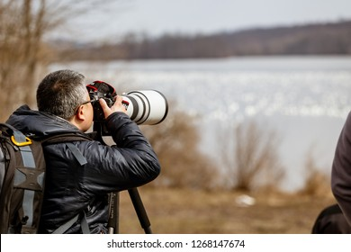 Kleinfeltersville, PA, USA - March 6, 2016:  A photographer takes pictures of migrating snow geese at the Middle Creek Wildlife Management Area, located at the Lebanon and Lancaster County border.