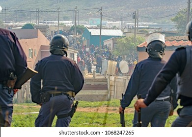 Kleinmond, Western Cape, South Africa, September 11th 2017. With the crowd baiting them, members of the riot police keep close watch on violent protesters during illegal protest action and riots.