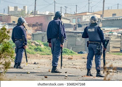 Kleinmond, Western Cape, South Africa, September 11th 2017. Three armed policemen guard a public road after they dispersed violent protesters during illegal protest action and riots.