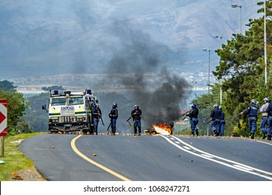 Kleinmond, Western Cape, South Africa, September 11th 2017. Members of the riot police rally behind an armored riot vehicle  during illegal protest action and riots.