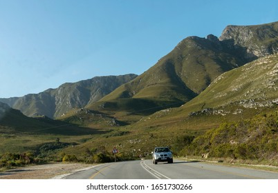 Kleinmond, Western Cape, South Africa. Dec2019.  The Hottentots Holland mountains overlook Clarence Drive, the R44 highway and car close to Kleinmond in evening light.