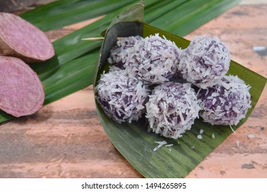 Klepon Ubi Ungu, Indonesian traditional dessert or Jajanan Pasar. Purple sweet potato glutinous rice balls stuffed with palm sugar coated with steamed desiccated coconut. Served on banana leaf