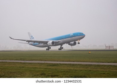 A KLM Airbus A330-300 is landing in the mist at Schiphol Airport. The aircraft registration is PH-AKB. Amsterdam, Netherland / November 16, 2018