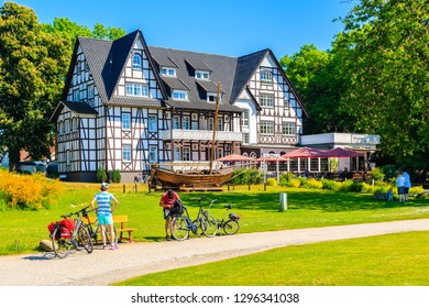 KLOSTER VILLAGE, HIDDENSEE ISLAND - MAY 30, 2018: Tourists on bikes and view of traditional restaurant and hotel in park. It is a car-free island in the Baltic Sea, Germany.