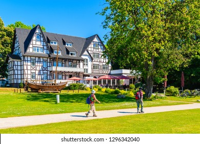 KLOSTER VILLAGE, HIDDENSEE ISLAND - MAY 30, 2018: Tourists walking on park path and view of traditional restaurant and hotel in park. It is a car-free island in the Baltic Sea, Germany.