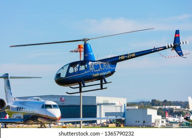 Kloten, Switzerland - September 29, 2016: a Robinson R44 Raven II helicopter landing at Zurich airport. The Robinson R44 is a four-seat light helicopter produced by Robinson Helicopter company.