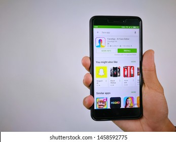 Kluang, Johor / Malaysia - July 23, 2019: Hand holding smartphone with FaceApp (portrait editor) for download showned on Play Store app for Android smartphone displayed on screen on white background.