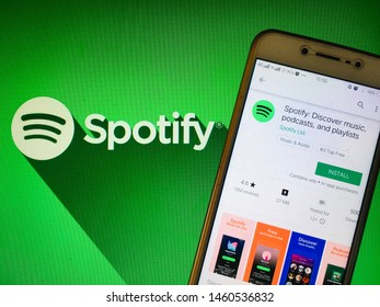 Kluang, Johor / Malaysia - July 24, 2019 : A man holding the Spotify app in front spotify wallpaper. Spotify music application, spofity apps in apple store and google play store.