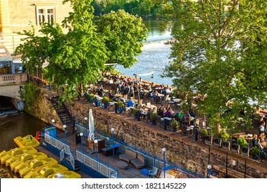 Klub Lavka restaurant in Prague. People are resting on a summer terrace overlooking the Vltava River. Prague / Czech Republic - 05.21.2019