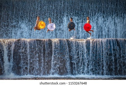 Klungkung, Bali - July 29, 2016: Four Balinese boys playfully performing for tourists in the manmade waterfalls of a dam on the Tukad Unda river.
