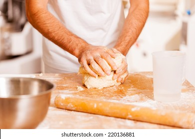 Kneading the dough. Close-up of male baker kneading the dough