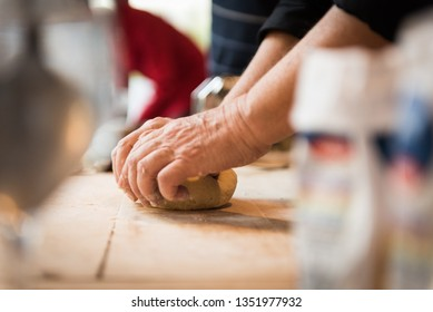 Kneading dough for fresh pasta of Italian agnolotti on a wooden cutting board