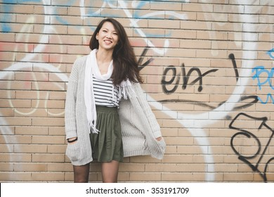 Knee figure of young handsome asiatic chinese woman posing against a brick wall, looking in camera smiling, hands in pocket - youth, happiness, carefree concept