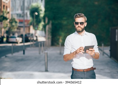 Knee figure of young handsome bearded businessman holding a tablet, looking over wearing sunglasses - technology, business, work concept, copy space left