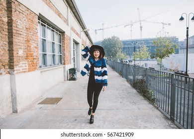 Knee figure of young handsome eastern woman walking outdoor in the city, wearing an hat, looking in camera smiling - happiness, youthful, carefree concept