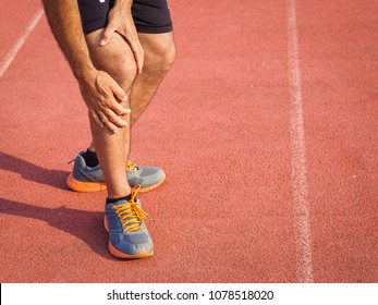 knee Injuries. sport man with strong athletic legs holding knee with his hands in pain after suffering muscle injury during a running workout training on Running Track. Healthcare and sport concept.