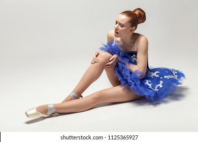 knee pain. ballerina with bun collected hair wearing blue dress and pointe shoes holding on injured knee while sitting on white floor. indoor, studio shot.
