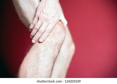 Knee Pain, man holding leg, making massage with hands. Physical injury and recovery or rehabilitation concept.