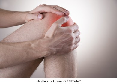 Knee pain in men on gray background