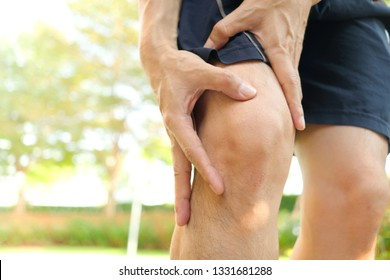 Knee pain .man sitting on the bed  Her hand caught at the knee. Having painful feet and stretching muscles fatigue To relieve pain. health concepts.