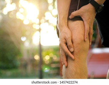 Knee pain .man stand at park Her hand caught at the knee. Having painful feet and stretching muscles fatigue To relieve pain. health concepts