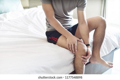 Knee pain, young man holding knee in the bedroom