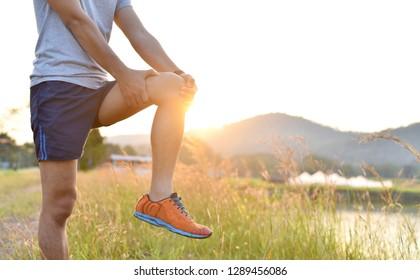 Peinture au genou ou ou blessure, Muscle de la jambe étirée, gros plan sur un jeune homme pendant l'exercice au coucher du soleil au parc