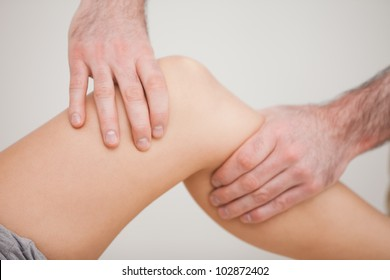 Knee of a patient being touched by a practitioner in a room