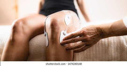 Knee Physical Therapy with TENS Electrode Pads, Transcutaneous Electrical Nerve Stimulation. Therapist Positioning Electrodes onto Patient's Knee