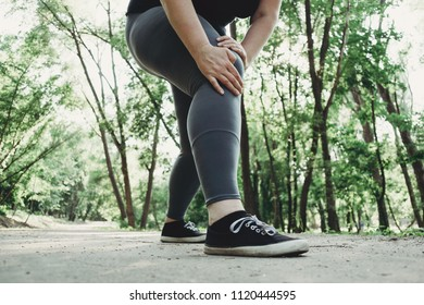 knee trauma, joint overload, excess weight. Fat woman holding injured leg at outdoor jogging