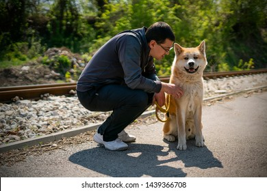 Kneeling man is cuddling orange akita dog on the yellow leash next to the railroad. Akita dog is looking at camera, and the background is blurred. The man and the dog cast shadows.