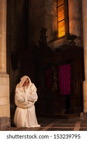 Kneeling and praying monk in a dark medieval church