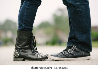 Knees down photo of a couple in an embrace facing each other in jeans and bad ass leather shoes.
