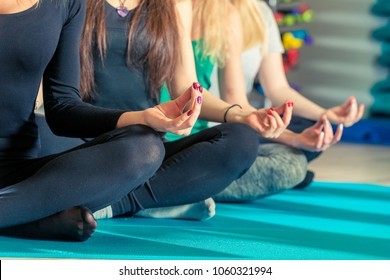 knees and hands of women sitting in a lotus pose in the gym close up