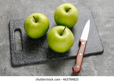 Knife and apples on cutting board.