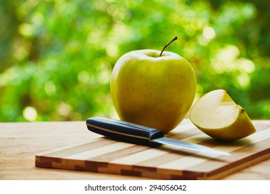 Knife and apples on the wooden cutting board on green blurred background