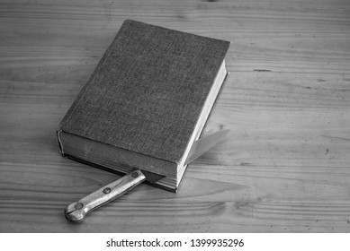 a knife between the pages of a book, black and white