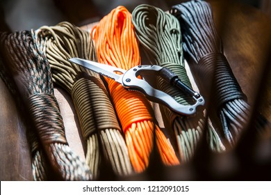 knife carbine and paracord, hanks of rope of different colors for weaving and tying tool camp in the forest