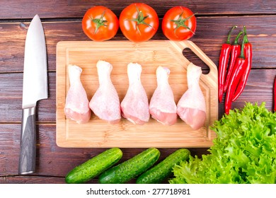 Knife, chicken legs and vegetables on an old table: tomatoes, cucumbers, pepper, onions, lettuce leaves