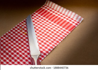 Knife for cutting bread on red pöti checkered cloth. Special illuminated environment.